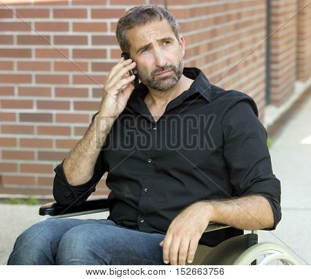 handsome man in wheelchair talking on his phone and looking sad