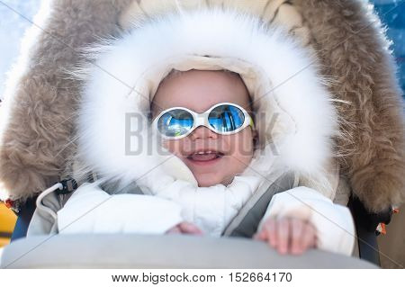 Little baby in warm stroller wearing fur hood snow suit enjoying winter ski vacation in alpine resort. Eyewear and sun protection sunglasses for infants. Child in safe snow goggles in Alps mountains.