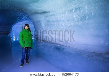 Child visiting ice cave tunnel in Swiss Alps glacier. School kid walking in ice tunnel in the mountains. Beautiful view of Aletsch glacier Switzerland. Tourist on winter vacation.