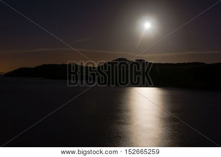 Hunter's moon over sea at Sand Point. Full moon reflected in water of Bristol Channel at high tide in Somerset England UK with clouds and coast