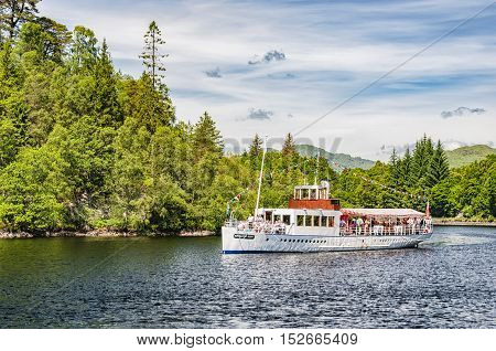 LOCH KATRINE SCOTLAND - July 09: The Sir Walter Scott steamship brings its passengers back to dock after a tour of Loch Katrine in Scotland.