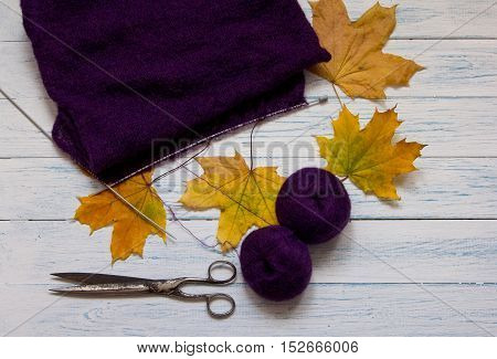 Violet yarn knit fabric knitting needles scissors and yellow fallen leaves are on white vintage wooden desk. Top view.