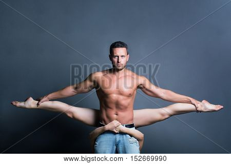 young sexy couple of handsome muscular man in jeans with bare torso holds pretty flexible woman or girl dancing contemporary or modern gymnastic dance in studio on grey background copy space