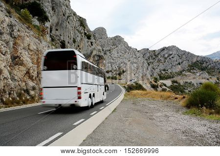 Tourist bus on winding road asphalt mountain highway with beautiful landscape on cloudy sky