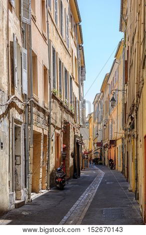 Romantic tiny street in central Aix-En-Provence South of France on hot summer day without pedestrians