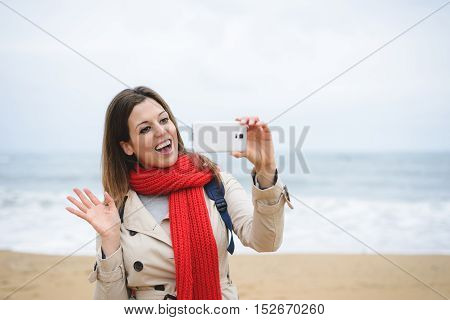 Woman Taking Selfie Photo With Smartphone And Waving