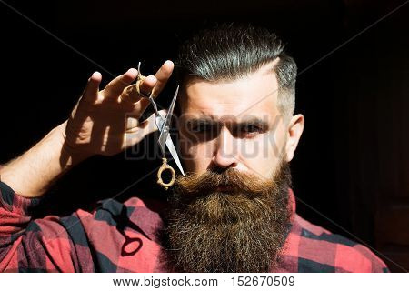 Adult man hipster with long beard and moustache in fashion chequered red shirt holding scissors near handsome sexy face on black background