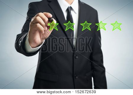 Review increase rating performance and classification concept. Businessman draw five green stars to increase rating of his company blank background.