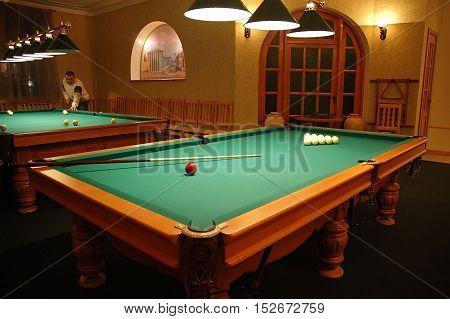 Kiev Ukraine - November 12 2006: Billiard interior in billiard club man playing in the pool background.