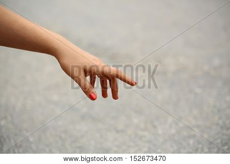 women or girl frail hand with red manicure on gray background