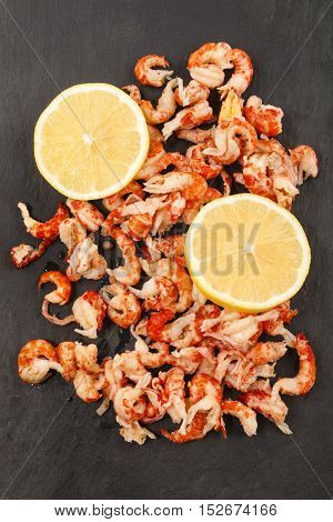 cleaned and cooked crayfish tails with lemon slice on slate