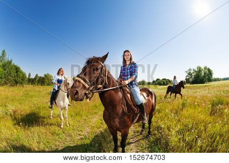 Three young female equestrians riding beautiful horses in flowery meadow