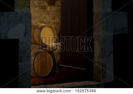 Barrels in a winery, through the door of cellar, Bordeaux Vineyard