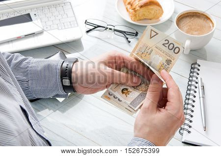 Businessman is counting money at breakfast in the work