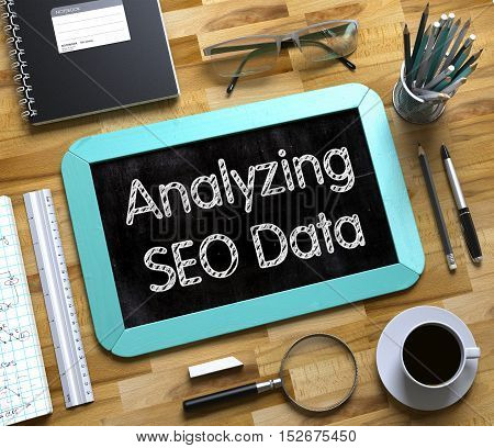 Analyzing SEO Data Concept on Small Chalkboard. Analyzing SEO Data Handwritten on Mint Small Chalkboard. Top View of Wooden Office Desk with a Lot of Business and Office Supplies on It. 3d Rendering.