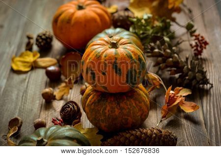 Autumn decorative pumpkins, fall leaves on a rustic wooden background, natural fall style decorations. Natural plenteous border background vintage mock up.