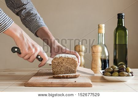 Bread cut by female hands in the kitchen. Female hands cutting whole wheat bread on wood board. Wood table with salt, pepper, green olives, oil and vinegar in the background.