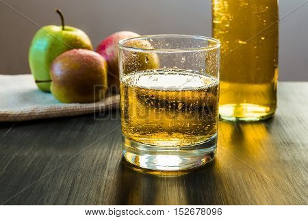Apple wine glass, apples, bottle of cider. Aparkling apple wine in a glass in front of fresh apples and a bottle of apple cider on wooden rustic table.