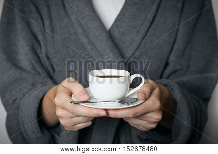 Giving a cup of coffee. Hands of female person in bathrobe holding cup of morning coffee in front of white wall.