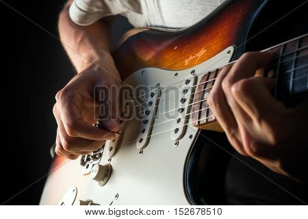 Vintage electric guitar closeup, male hands playing with a pick. Closeup photo of male hands playing vintage electric sunburst guitar with mint pickguard with pick in front of dark background.