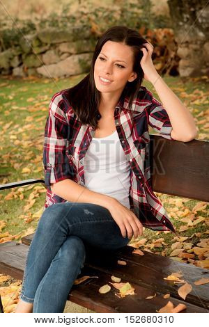 Beautiful young woman sitting on a bench in park at fall