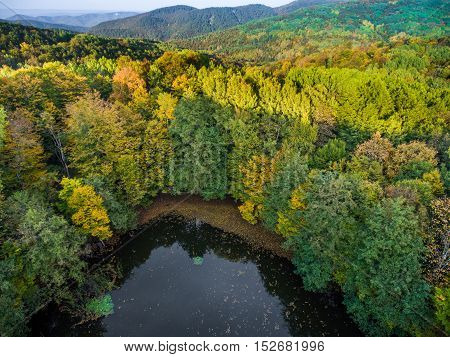 Wild lake in the autumn forest in the shadow of the mountain. Russia.