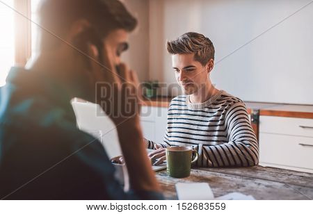 Young business owners at home talking on a cellphone and using a laptop while working together on their home based business