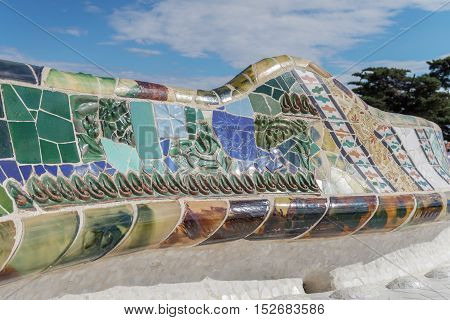 Barcelona, Spain - 24 September 2016: Park Guell mosaic seating at Nature Square Placa de la Natura. Mosaic seating area with multi-coloured tiles at at Nature Square Placa de la Natura.