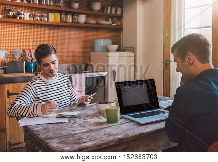 Young gay couple sitting at the kitchen table at home using a laptop and digital tablet while working together on their home based business