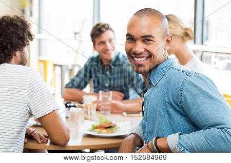 Portrait of happy african young man with his friends eating at cafeteria in background. Portrait of smiling guy looking at camera with friends eating burger.