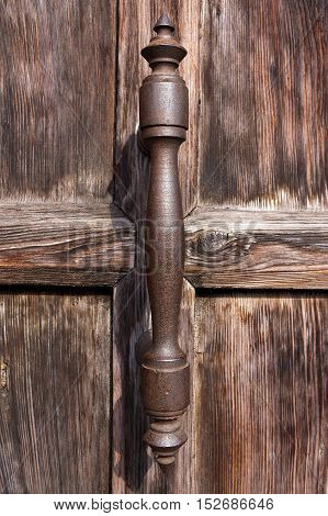 Detail of an old wooden door with a rusty iron handle in the city of Verona Veneto Italy