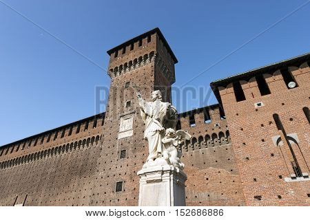 Sforza Castle XV century (Castello Sforzesco) in Milan Lombardy Italy with Tower of Bona and Giovia and statue of St. Giovanni Nepomuceno Bohemian priest