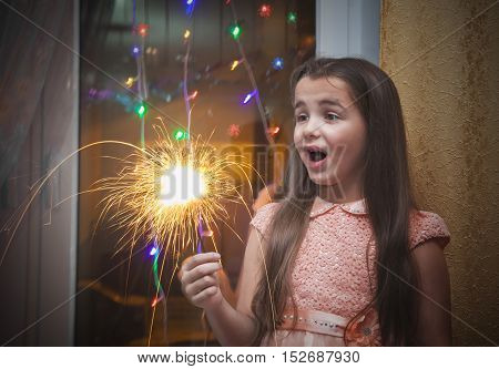 little suprised girl with long brown hair in pink dress holding a sparkler