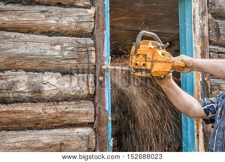 chainsaw man sawing a window in the repair of the house