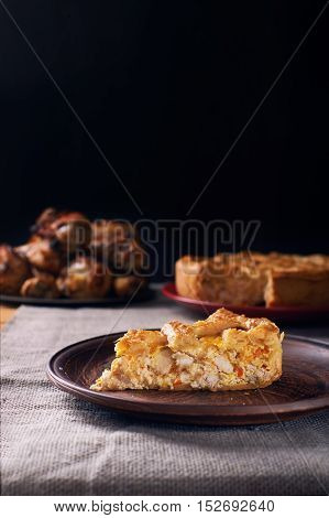 Piece of a chicken meat pie on plate on a black wooden background. Vertical shot. Dark photo