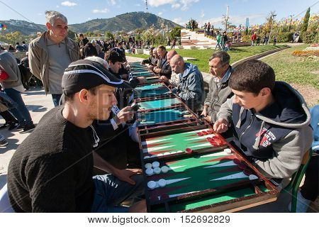 TBILISI, GEORGIA - OCT 16, 2016: Young men playing backgammon on competition at annual autumn city festival Tbilisoba on October 16, 2016. Tbilisoba is traditional festival in capital of Georgia from 1979