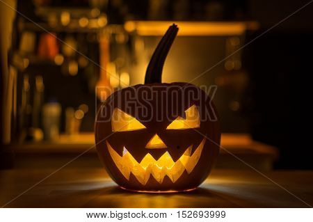 Halloween pumpkin head Jack o' Lantern illuminated on wood table.