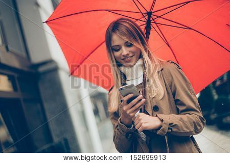 Typing message on the go. Attractive young smiling woman carrying umbrella and looking at her mobile phone while standing on the street
