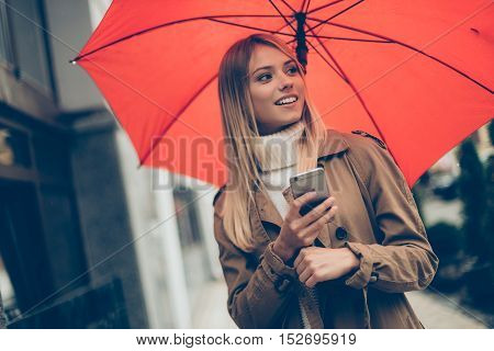 Beauty with umbrella. Attractive young smiling woman carrying umbrella and and mobile phone while standing on the street