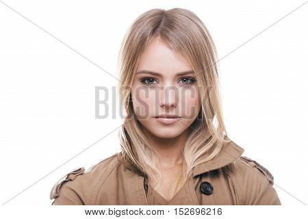 Woman in coat. Portrait of attractive young woman in coat looking at camera while standing against white background
