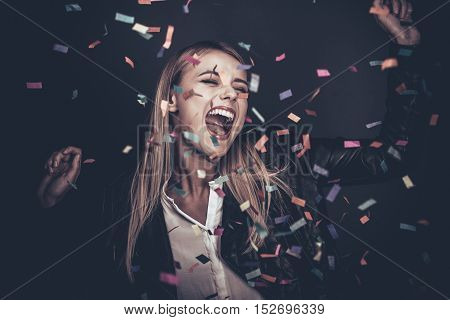 Confetti fun. Beautiful young woman throwing confetti and looking happy