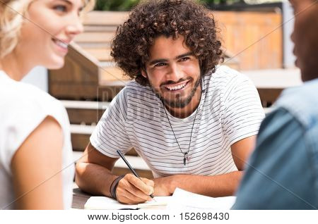 Happy young african man enjoying with friends after study. Smiling multiethnic guy with his friends studying outdoor in a summer day. Portrait of happy young man looking at friends.