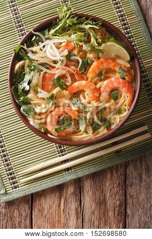 Malaysian Laksa Soup With Shrimps, Noodles And Herbs Close Up In A Bowl. Vertical Top View