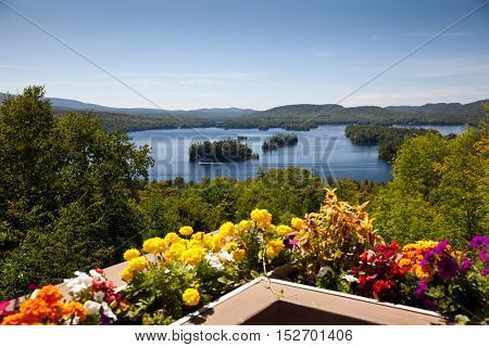 Beautiful colorful view on the mountains lake from balcony with yellow and red flowers