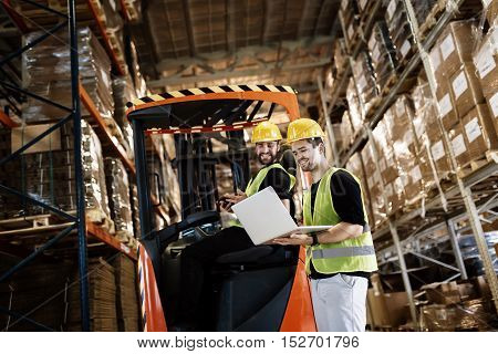 Workers using technology and forklift in warehouse