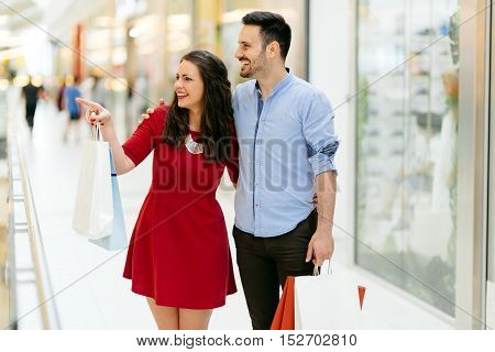 Happy shopper couple buying clothes in shopping center