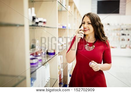 Happy young cute woman testing new fragrances