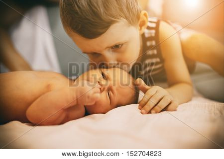 Brother kissing sweet little cute newborn sister