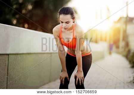 Fatigue of cute tired young female runner