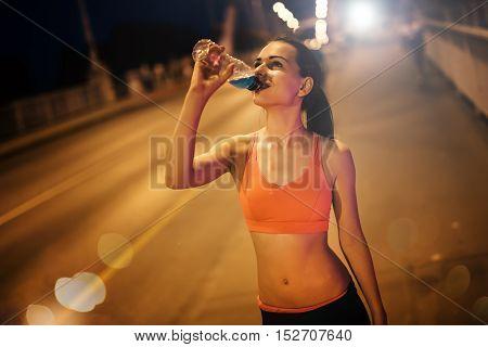 Thirsty beautiful sportswoman drinking water after workout